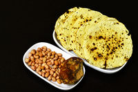Roasted papad an Indian snack with whole peanuts and jaggery in a plate