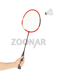 Hand with badminton racket and feather shuttlecock