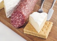 Snack with Brie Cheese And Salami On A Wooden Board