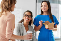 happy businesswomen eating take out food at office