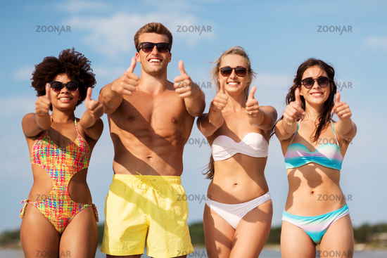 happy friends showing thumbs up on summer beach