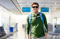 smiling man with backpack over airport terminal