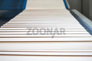 Folded Paper Signatures Coming out of Machine Conveyor Belt Printing Industrial Equipment