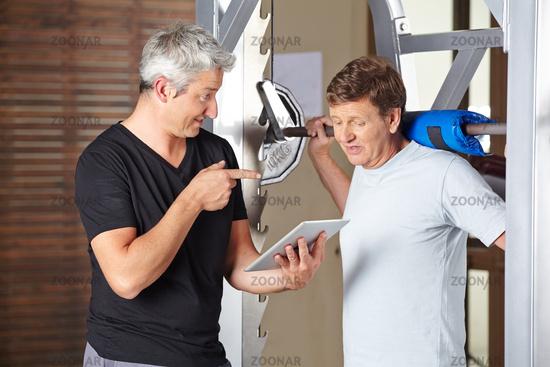 Fitnesstrainer mit Tablet Computer trainiert Senioren