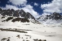High sunlit rocks, snowy plateau and cloudy blue sky