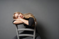 bored female sitting astride on chair and staring at ceiling
