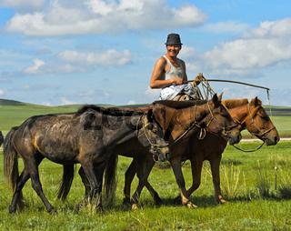 Hirt reitet auf einem Pferd in der Steppe, Mongolei