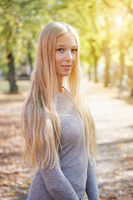 outdoor portrait of blond young woman enjoying sunny day