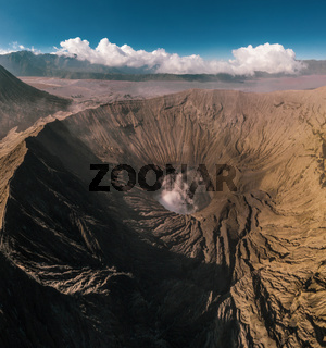 Cinematic shot aerial view of Mount Bromo crater with active volcano smoke in East Java