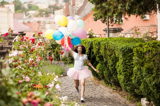Girl with colorful latex balloons in the park