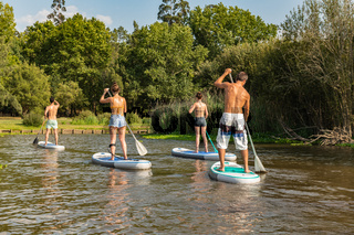 Man and women stand up paddleboarding