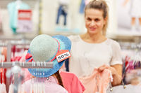 Frau und Kind beim Hut Kaufen