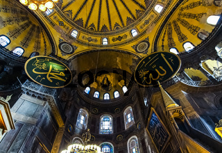 Bottom up interior view of the domed apse in Hagia Sophia with mosaic of Virgin Mary and Child