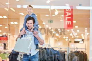 Mann mit Sohn im Huckepack beim Einkaufen