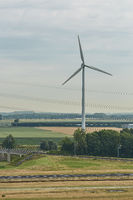 Windmills as wind turbine power generators placed within the countryside of green country of Netherl
