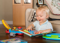 Infant caucasian boy reading book rather than using computer