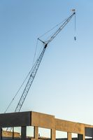 Construction crane towering over the concrete framework of unfinished building