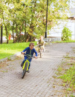 Two little boys ride a bike racing one another along paths of the park