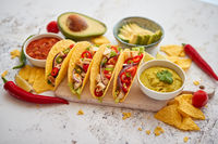 Tasty Mexican meat tacos served with various vegetables and salsa