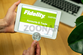 Businessman holding computer tablet with opened Fidelity website and Ethereum coin on a office desk