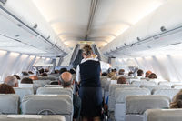 Interior of commercial airplane with stewardess serving passengers on seats during flight.
