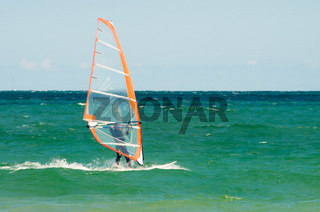 Windsurfing Man is worn on the blue sea against the background of a beautiful sky.