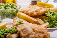 Traditional British street food fish and chips with mushy peas on paper plate