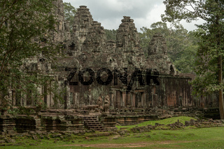 Facade of Bayon temple surrounded by trees