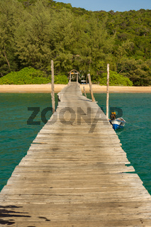 Standing on the end of a wonky wooden pier looking towards a paradise island.