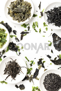 Dry seaweed, sea vegetables, shot from the top on a white background, forming a frame. A design template with a place for text