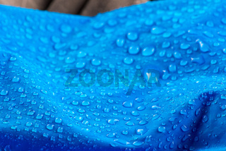 Nylon waterproof fabric with blurred background. Rain Drops on Water Resistant Textile waterproof coating background with water drops