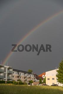 leuchtender Regenbogen ueber Wohnhaeuser - Hochformat