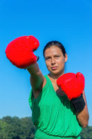 Young woman punches with red boxing gloves outside