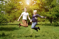 young couple jumping for joy in nature