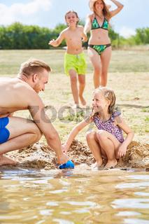 Mädchen baut mit ihrem Vater eine Sandburg