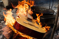 Guitar in flame and old sooty cauldrons on campfire