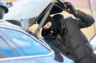 Dieb öffnet Koffferraum von Auto