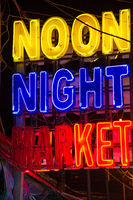 Bight colourful neon sign advertising a popular Noon Night Market in Siem Reap, Cambodia.