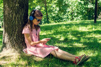 Girl listening to music under the tree