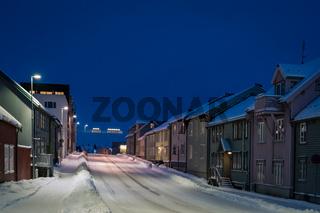 Empty snowy residential street in Tromso at dusk