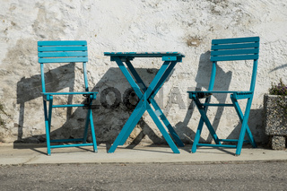pictoresque blue chairs on a street