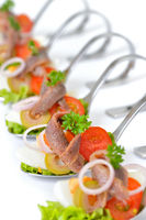 Fish appetizers on serving spoons