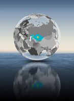 Kazakhstan on translucent globe above water