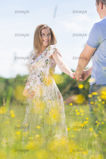 Young happy pregnant couple in love holding hands, relaxing in meadow.