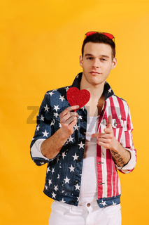 All-american cute guy holding a red heart in american flag jacket