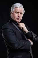 Mature man in black suit looking at the camera with a hypnotic look.