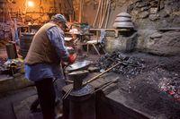 traditional blacksmith manually forging the molten metal