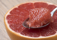 Half of Juicy Ripe Red Grapefruit with slice in a spoon. Close up view.