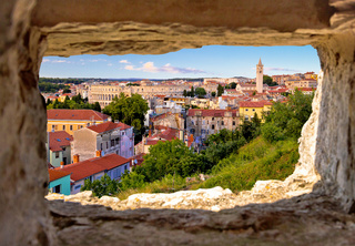 Panoramic view of Pula landmarks through stone window