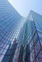 Blue glass skyscraper facade against sky